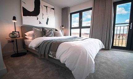 White bed with patterened pillows and throw