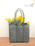 mexican woven bags in black made from plastic carrying yellow tulips