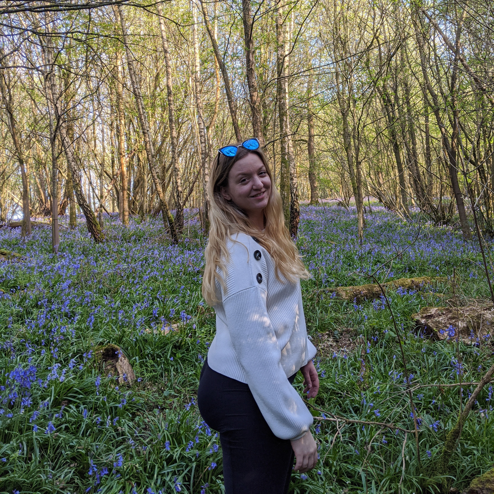 Hannah Schaapkens in the Bluebell woods with sunglasses on her head and wearing a white jumper