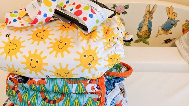 Stack of reusable cloth nappies and work pass on Peter Rabbit changing table