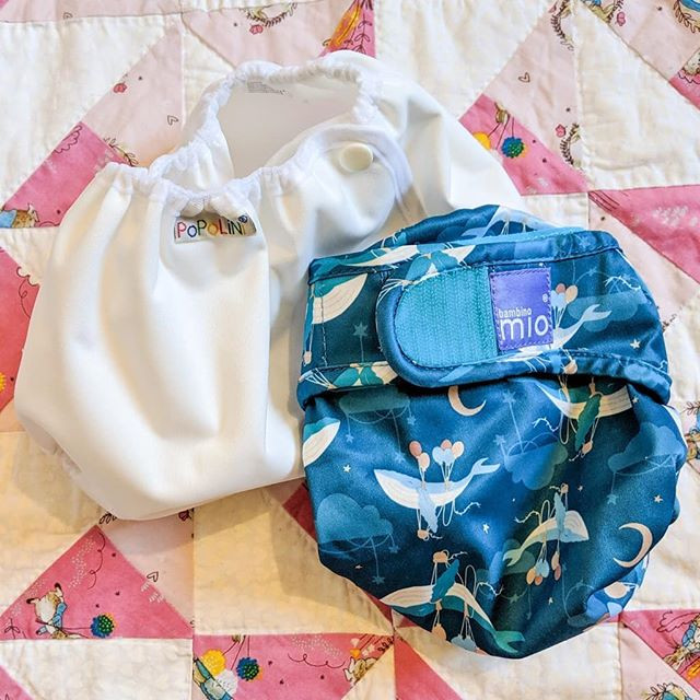 Two different cloth nappy wraps for covering fitted or flat nappies