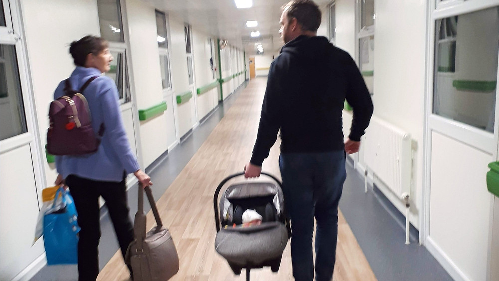 Dad carrying his newborn baby out of the hospital
