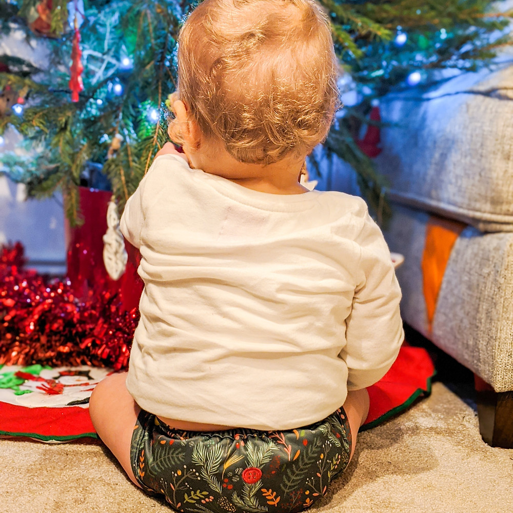 Baby girl sitting in front of a potted Christmas tree wearing a Buttons Diaper