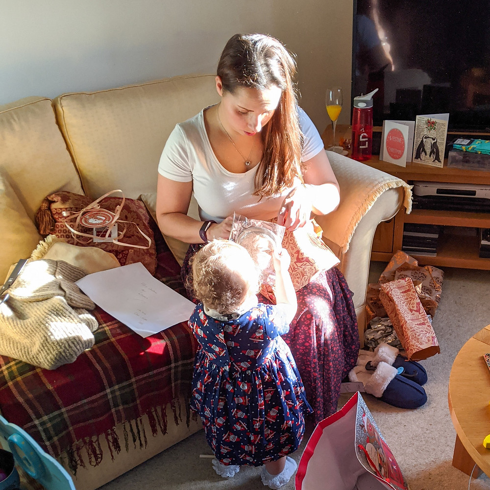 Mum and her baby opening Christmas presents