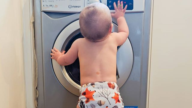 Baby stood in front of Indesit washing machine wearing a Motherease Wizard Uno reusable nappy in Foxy print