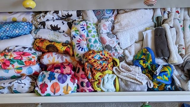 Drawer filled with cloth nappies, wraps, inserts, boosters and liners