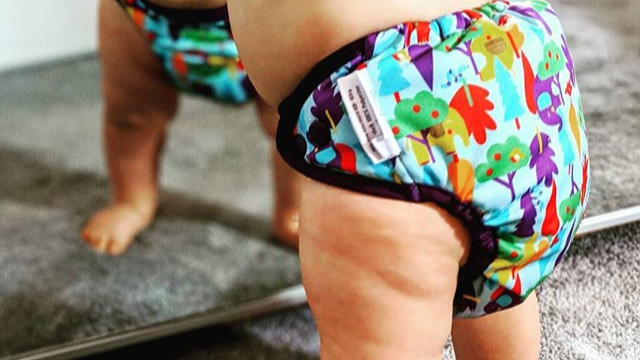 Baby standing in front of a mirror wearing a Close Pop-in cloth nappy in Hydref print