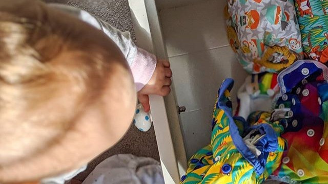 Baby pulling modern cloth nappies out of a drawer