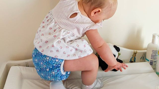 Baby yoga pose wearing Tickle Tots cloth nappy in scales