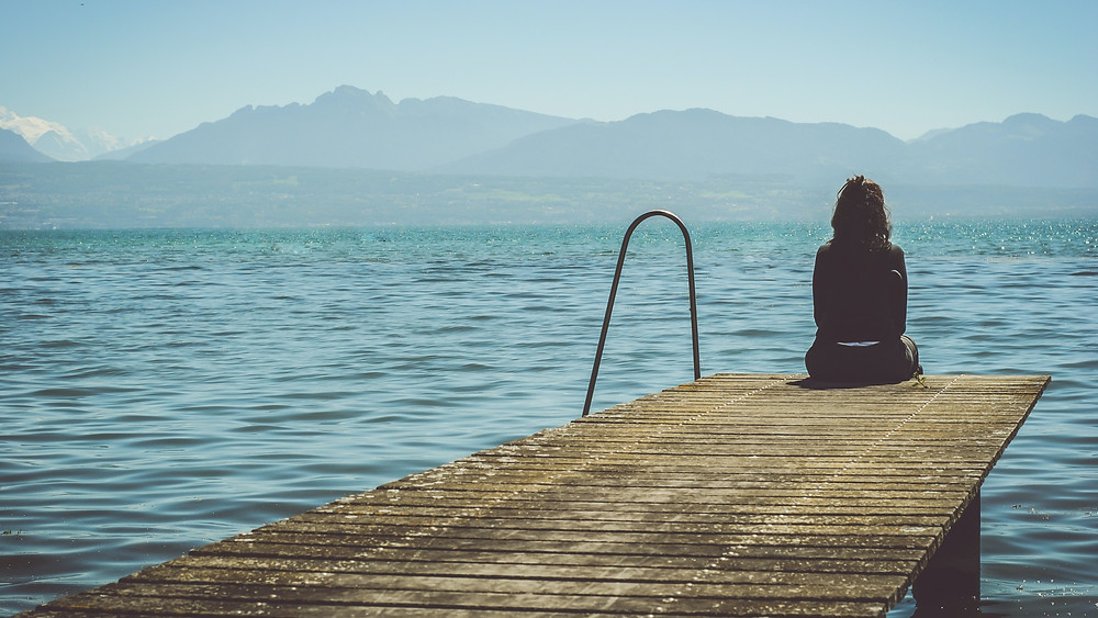 Woman struggling to conceive looking out to sea