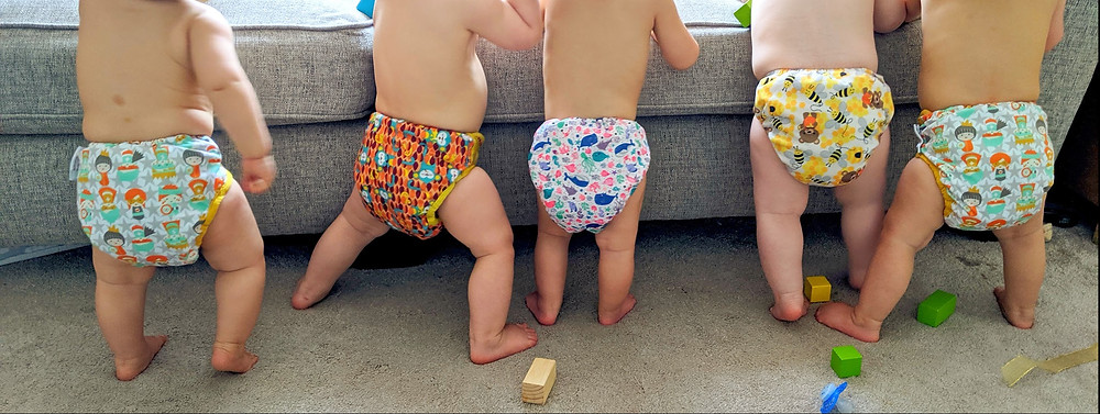 Babies stood up wearing different reusable nappies
