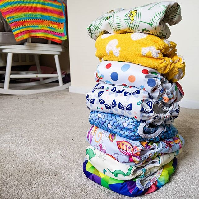 Colourful stack of modern cloth nappies in baby's nursery