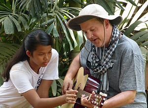 Cambodian children teaching Americans guitar
