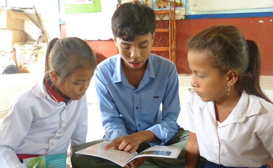 Lionel from Sovann Komar helps two girls from Kampong Thom understand the story
