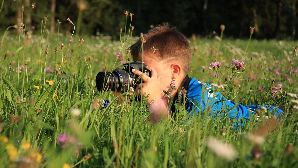 boy taking photo in meadow crop.jpg