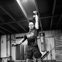 John Withinshaw demonstrating a kettle bell shoulder press in black and white