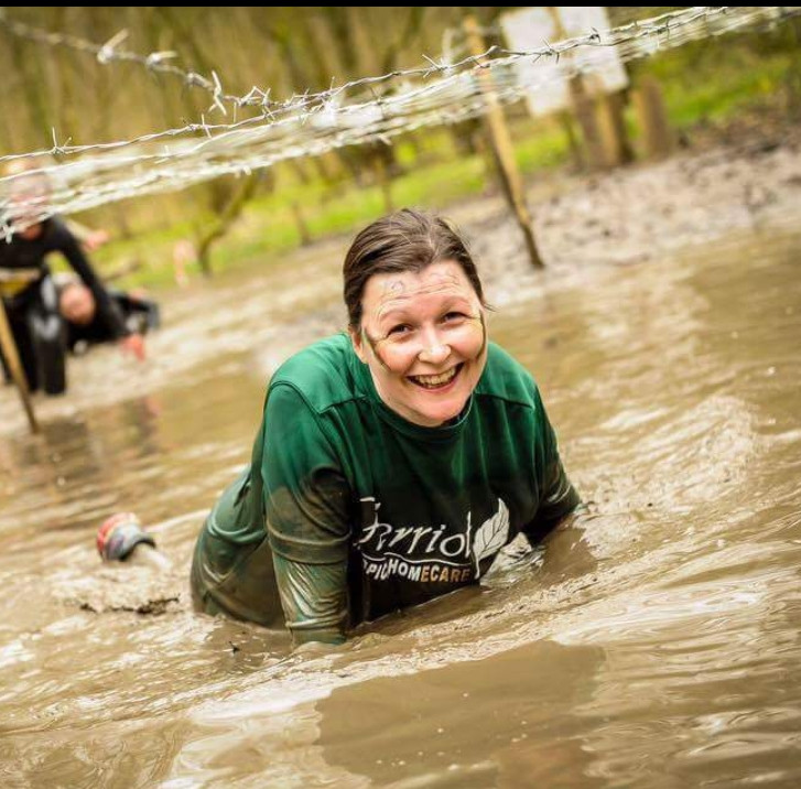 JDW Fitness private client crawling through water at the Major Series obstacle race with a big smile on her face