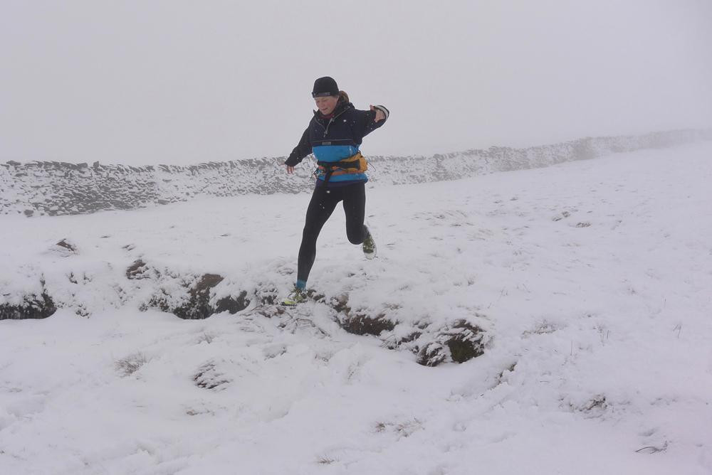 Female Ultra fell runner in the snow on Plover Hill, the Yorkshire Dales
