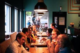 Mehrere Menschen, die sich gut unterhalten, an drei Tischen in einer Bar.