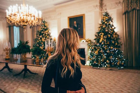 Frau in einem Zimmer mit zwei geschmückten Weihnachtsbäumen im Hintergrund