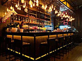 Eine Bar mit Barstühlen und leerem Tresen. Dahinter sieht man das große Spirituosenregal.