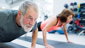 senior-couple-gym-working-out-doing-musc
