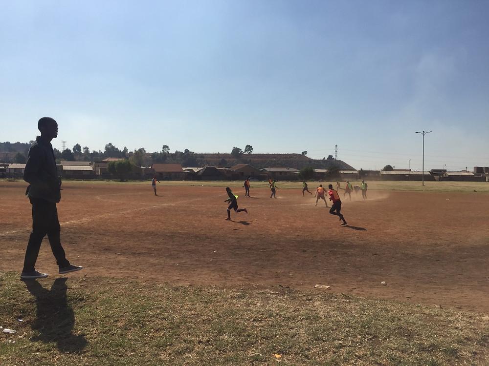 Dirt field Meadowlands locals play football