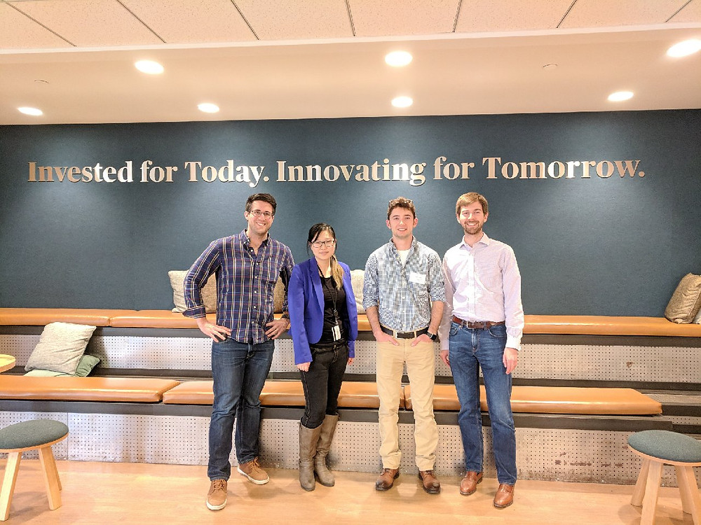 """Four team members of Honeycomb Credit standing side-by-side in front of a wall reading, """"Invested for Today. Innovating for Tomorrow."""""""