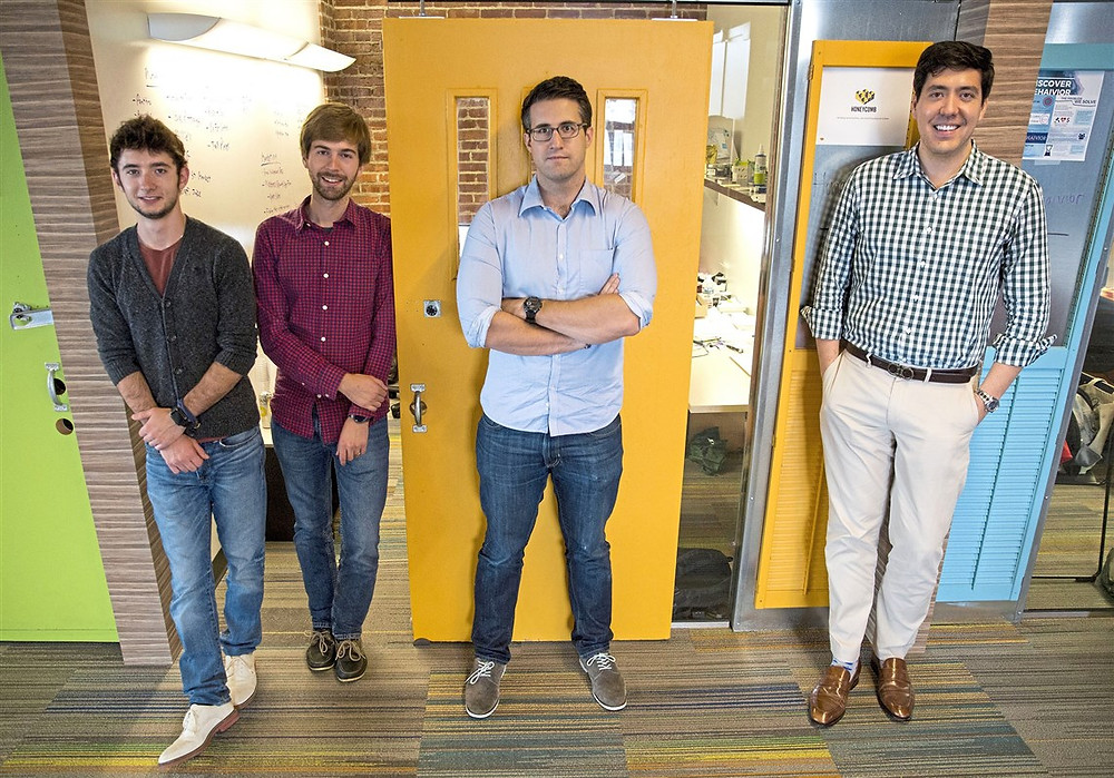 Four of the Honeycomb Credit founders and employees stand side-by-side in the office