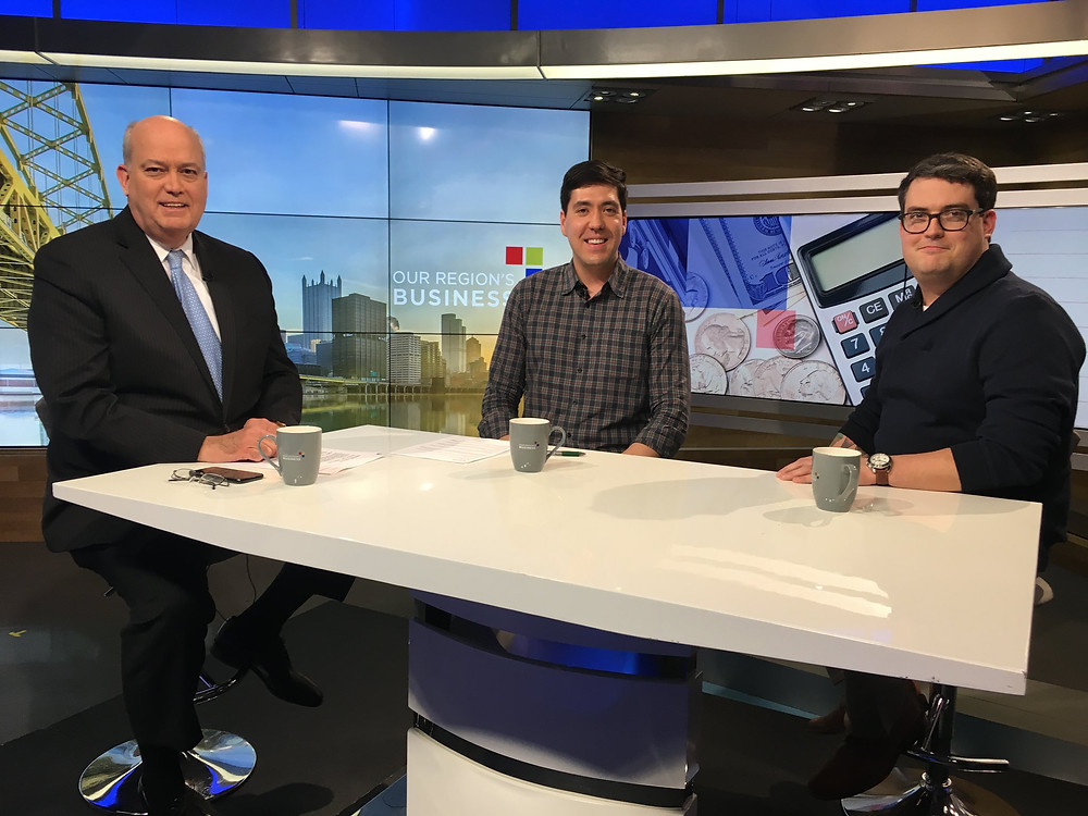 Honeycomb Co-Founder, Ken Martin, and Millie's Homemade Ice Cream Owner, Chad Townsend behind a desk while featured on a business affairs television program