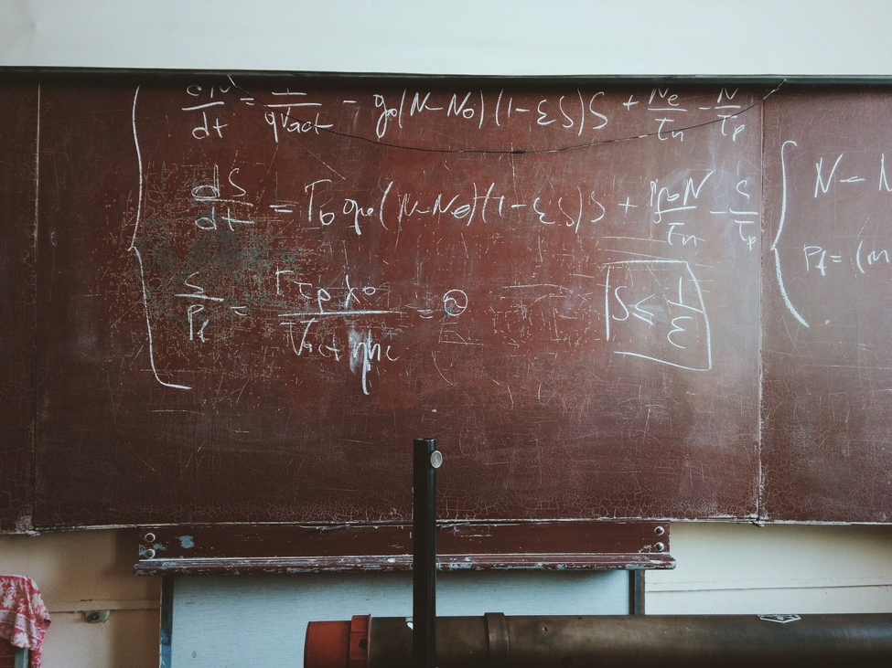 A brown, used chalkboard with formulas written out in a classroom