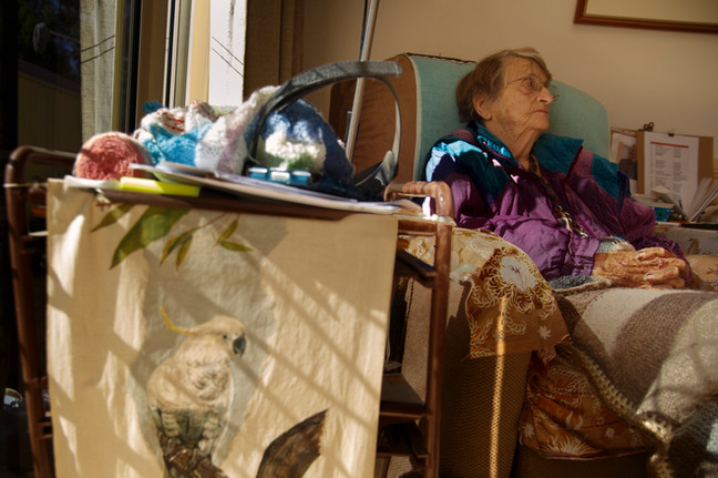 Grace Lithgow of Chinchilla rests on her favourite chair in the lounge amongst various artworks and knitted blankets.
