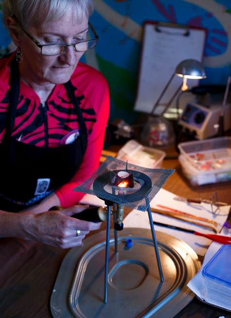 "Carol Money of the ""Missabittatitti"" dragon boat team prepares enamel for her jewellry making endeavours.  Dragons Abreast Brisbane is a community support and sporting group where women who have survived breast cancer are able to meet new friends, gain mutual support and camaraderie and keep fit in a sporting environment."