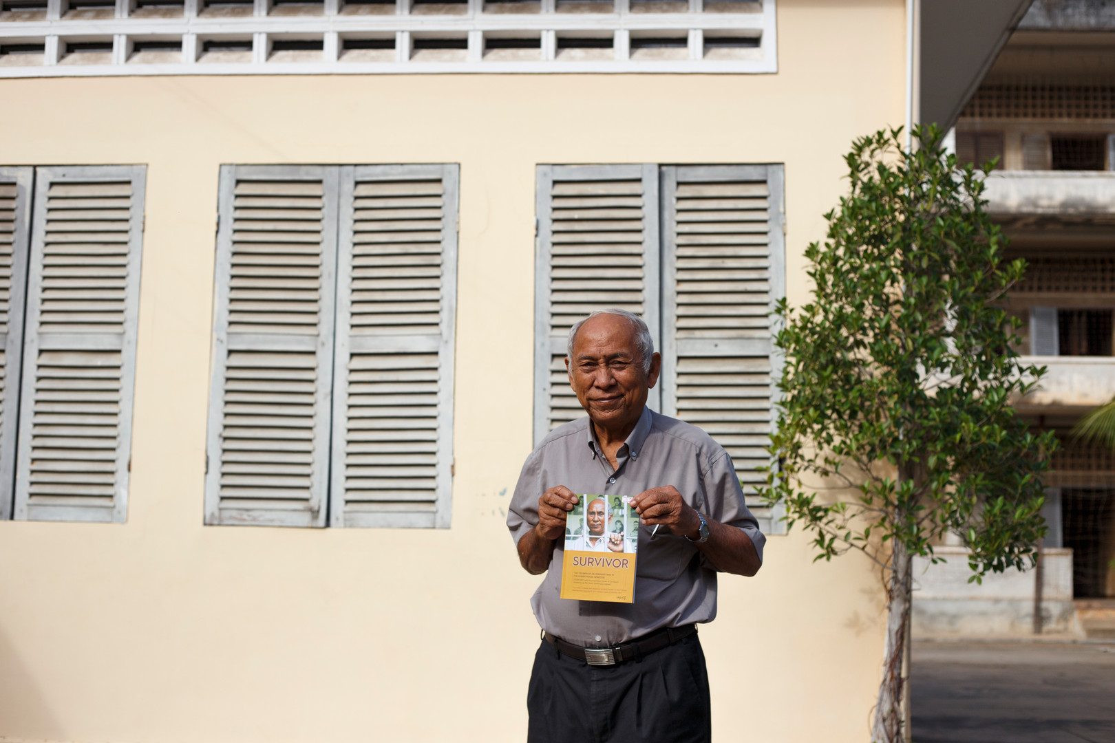 Chum Mey, survivor of the Khmer Rouge and former political prisoner at the Tuol Sleng centre stands in front of the main building with a copy of his memoir.