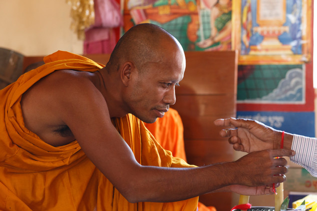Monk Louhong Ply fits a bracelet to the wrist of Khmer Rouge survivor Klav Kleum during a testimonial therapy ceremony organised by the Transcultural Psychosocial Organisation at Ta Ann Village, Ta Ann Commune, Cambodia on the 18th of January 2018.
