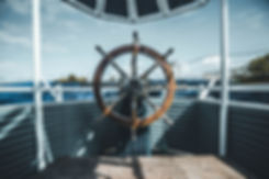 wooden helm of a boat at sea