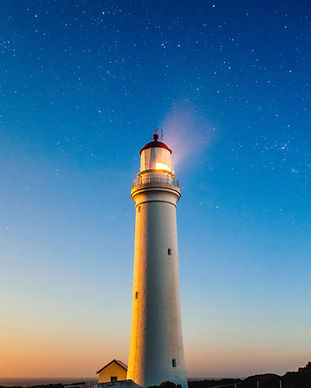 lighthouse shining in the nightsky
