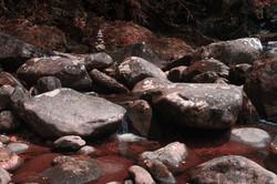 Rio corre entre pedras, na paleta de Magritte