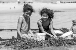 Crianças brincando com redes e peixes