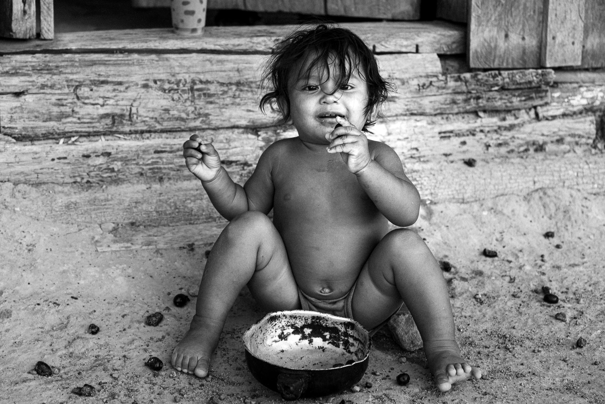 Criança wapichana brincando e comendo