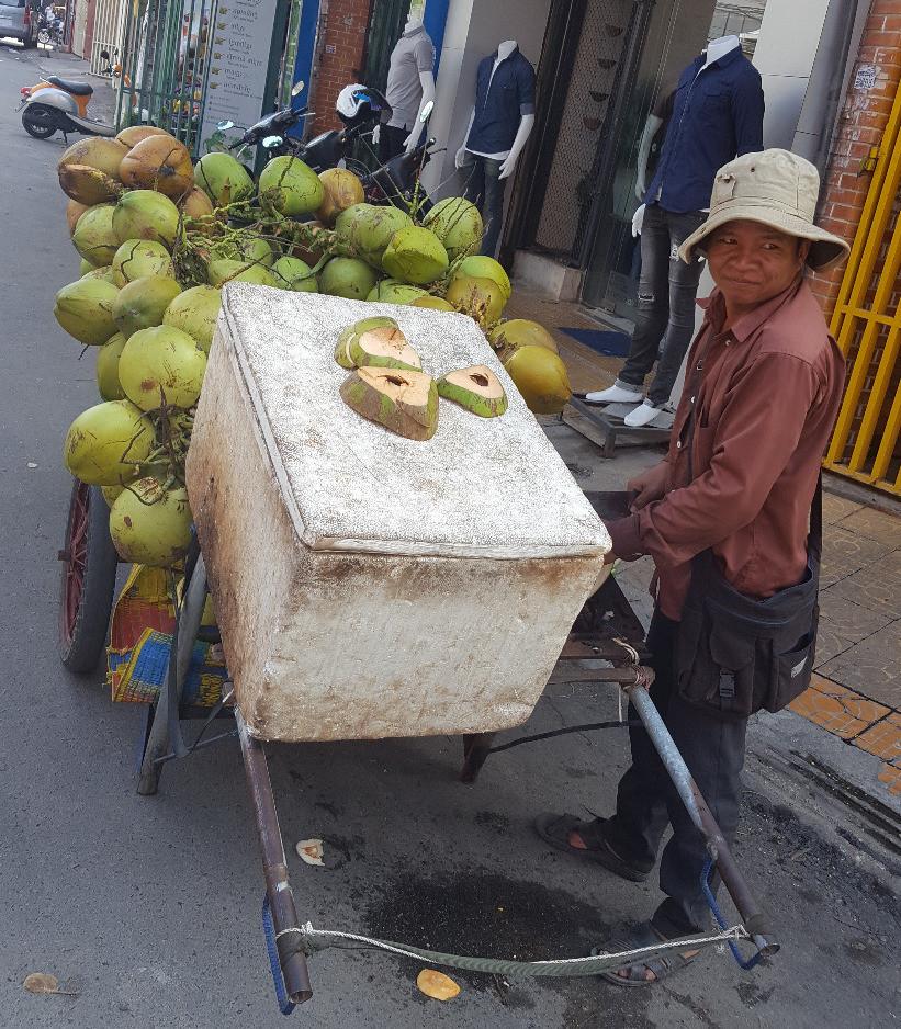EIn Kokosnussverkäufer mit seinem schweren Wagen