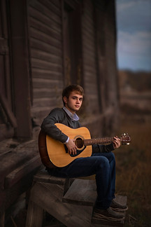 High school guy with guitar during senior photos in downtown Waxahachie Texas