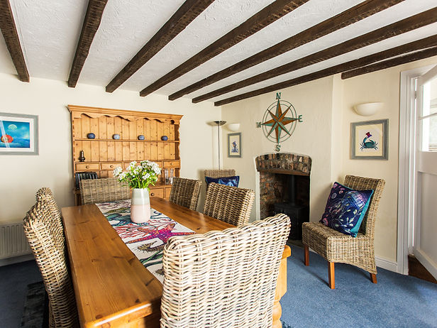 Catboat Cottage dining room with 8 wicker chairs, beamed ceiling and old stone fireplace