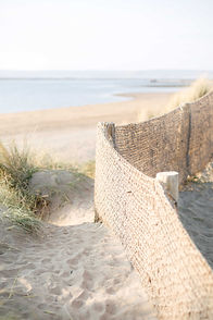 View through the sand dunes at Instow onto the beach with the sea on the horizon.