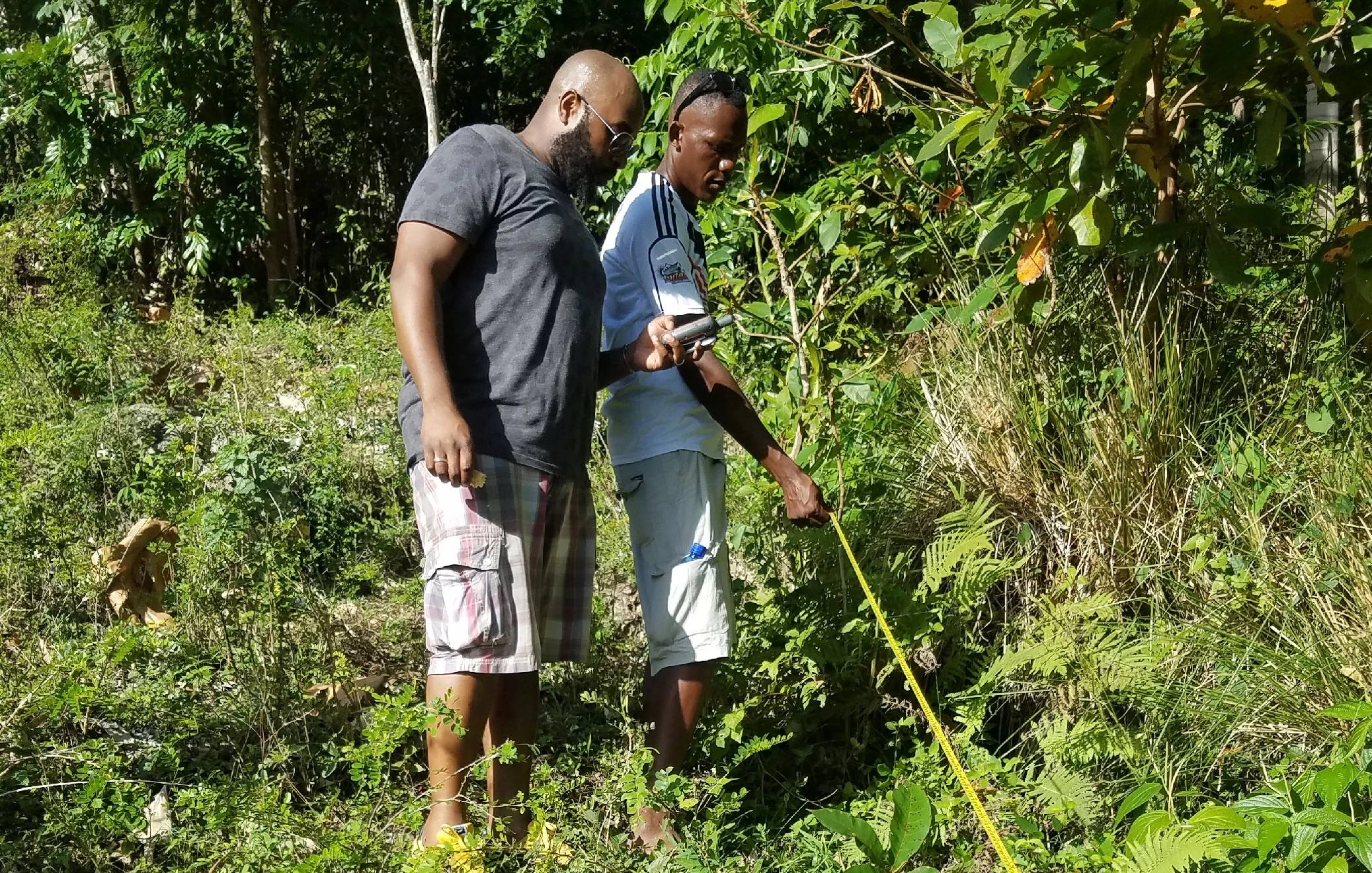 DCC Chair Gardy Guiteau conducting site mapping of the first of three pathways for the irrigation system at Bassin Bleu, Jacmel.
