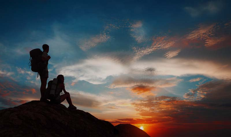 Backpacker hikers on mountian at sunset
