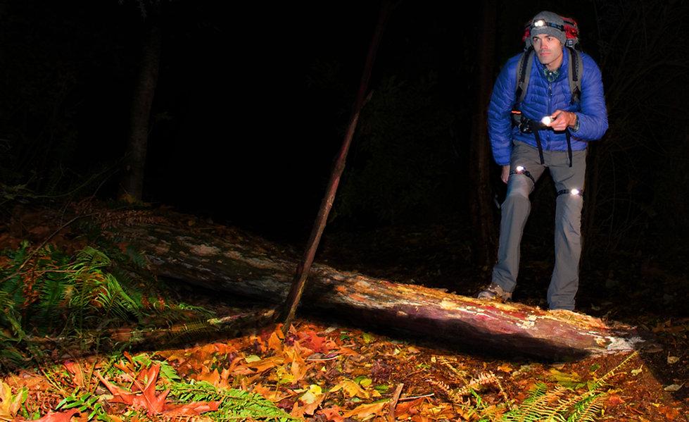Hiker trekker wearing LED headlamp, flashlights, and LEGLIGHTS