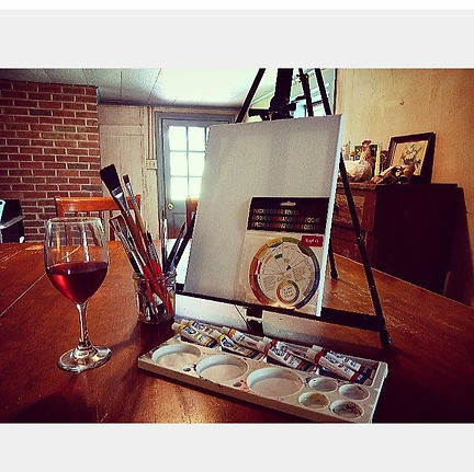 A glass of wine, canvas, paints, and brushes for a paint and sip party