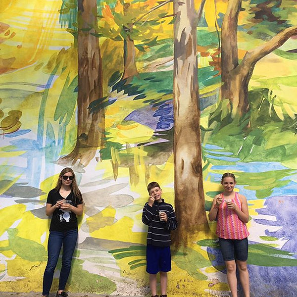 kids standing in front of a beautiful mural of trees.