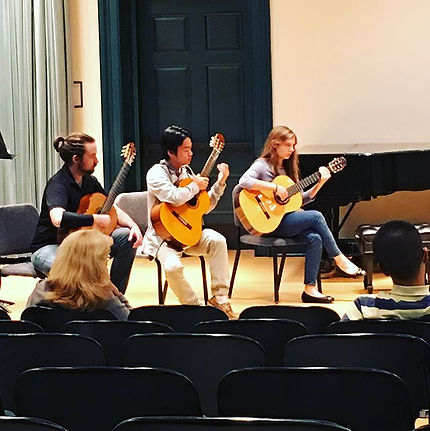 two men and a woman playing classical guitar